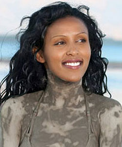 girl with dark curly hair in mud