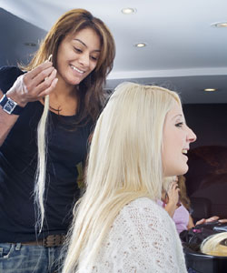 stylist holding strand of hair extensions