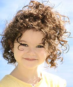 a beautiful little girl with curly frizzy hair in beach