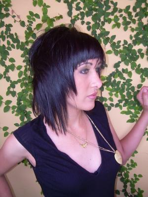 A layered hair style with razor cut choppy ends and a short straight bangs